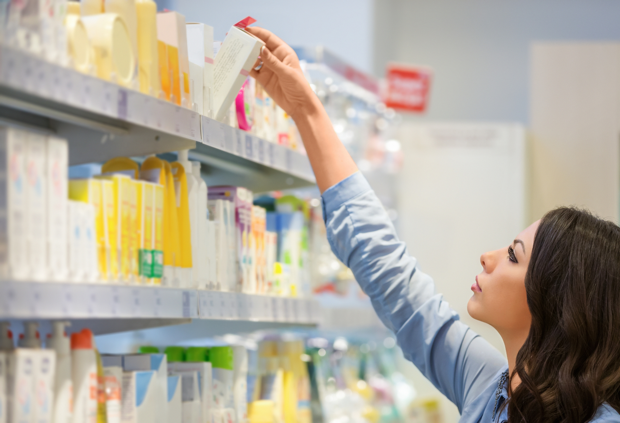 Woman reaching for body lotion in department store